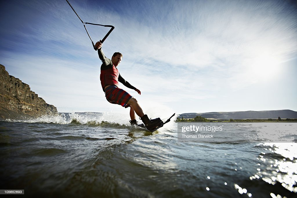 Man carving turn on wakeboarding view from water : Stock Photo