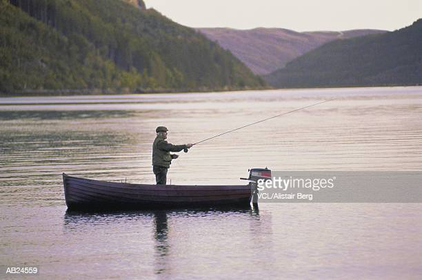 Man casting fishing line into lake