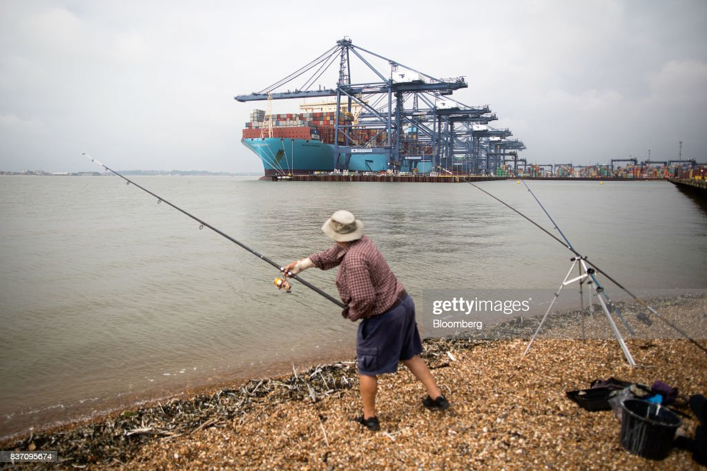 A man casts a fishing rod as the Maersk Madrid container ship, operated by A.P. Moller-Maersk A/S, sits docked at the Port of Felixstowe Ltd., a subsidiary of CK Hutchison Holdings Ltd. in Felixstowe, U.K., on Tuesday, Aug. 22, 2017. U.K. exporters are still reaping the benefits of a weaker pound, but they're not sure how long the boost will continue as the country gets closer to withdrawing from the European Union. Photographer: Simon Dawson/Bloomberg via Getty Images