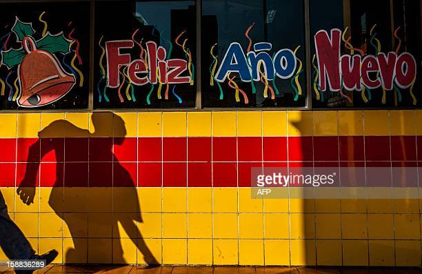 A man casts a shadow next to a window with the words 'Happy New Year' painted on it in Havana on December 31 2012 AFP PHOTO/YAMIL LAGE