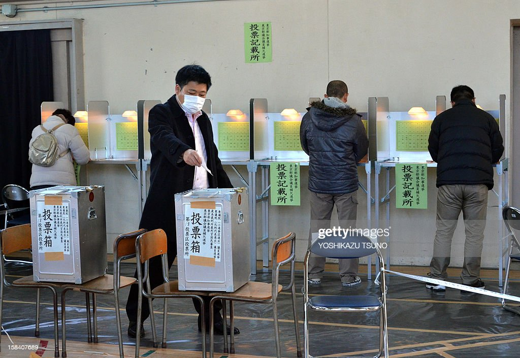 A man (2nd L) casts a vote in Japan's general election at a polling station in Tokyo on December 16, 2012. Voters began casting ballots in Japan for a general election likely to return long-ruling conservatives to power after three years in the wilderness. AFP PHOTO / Yoshikazu TSUNO