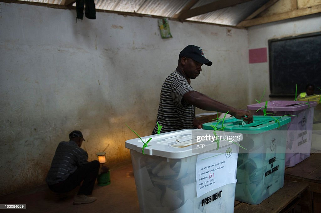 A man casts his ballot as an election officer lights a kerosene lamp at the Oloolua Primary School as voting closes in the town of Ngong, outside of Nairobi in Kenya on March 4, 2013, the day of the Kenyan national elections. Long lines of Kenyans queued from way before dawn to vote Monday in the first election since the violence-wracked polls five years ago, with a deadly police ambush hours before polling started marring the key ballot. The tense elections are seen as a crucial test for Kenya, with leaders vowing to avoid a repeat of the bloody 2007-8 post-poll violence in which over 1,100 people were killed and observers repeatedly warning of the risk of renewed conflict.