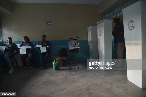 TOPSHOT A man casts his ballot at polling station at the Lycee National of Petion Ville in the commune of Petion Ville PortauPrince on January 29...