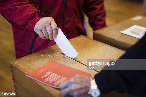 A man casts his ballot during a nationwide popular vote on February 9 2014 at a polling station in Ascona Swiss voters decide whether to curb...