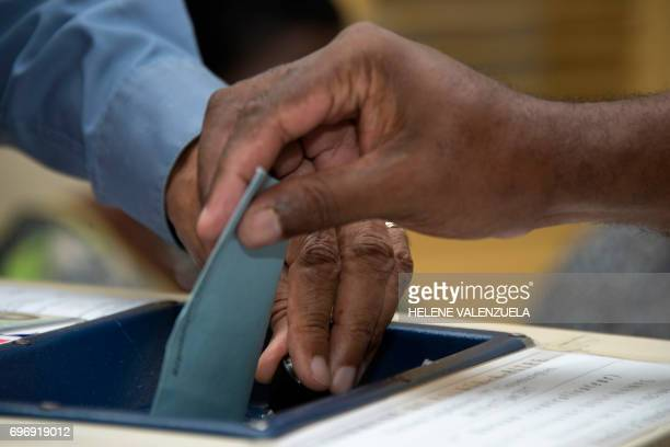 A man casts his ballot during the secound round of the French legislative elections at a polling station in PointeaPitre on June 17 2017 / AFP PHOTO...