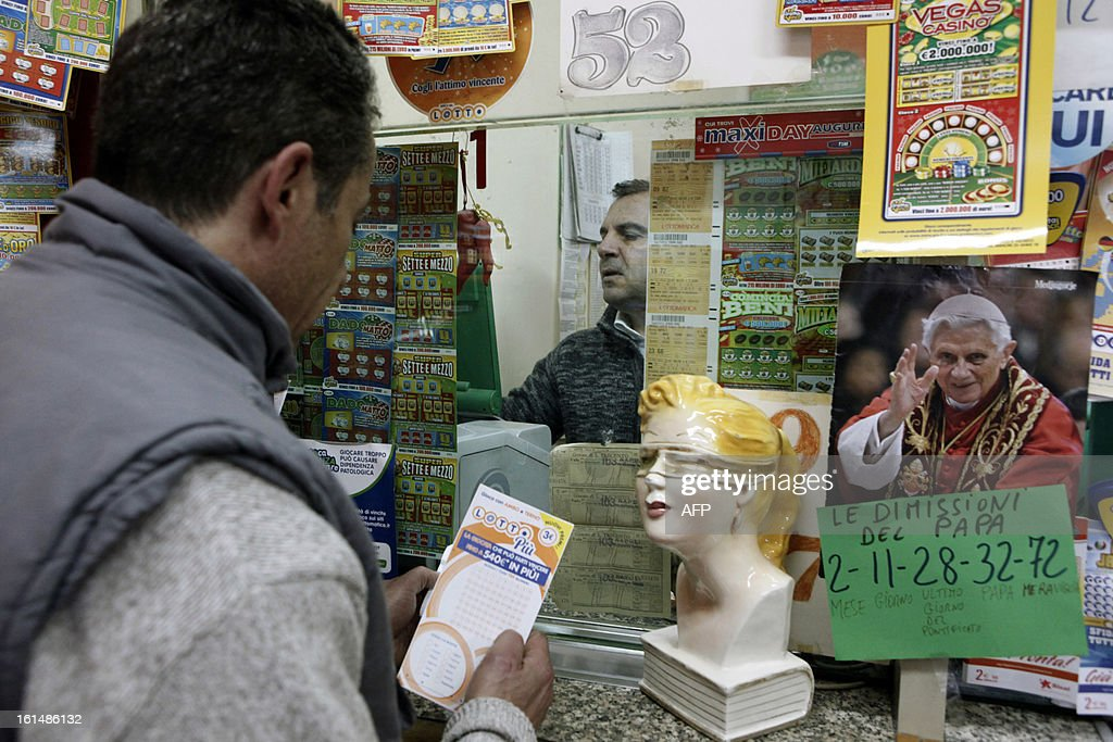 A man casts his lottery ticket while a placard with lucky numbers is attached to a portrait of Pope Benedict XVI in a lottery shop in Naples after the pontif announced his resignation on February 11, 2013. The placard shows numbers associated to the resignation of the Pope.