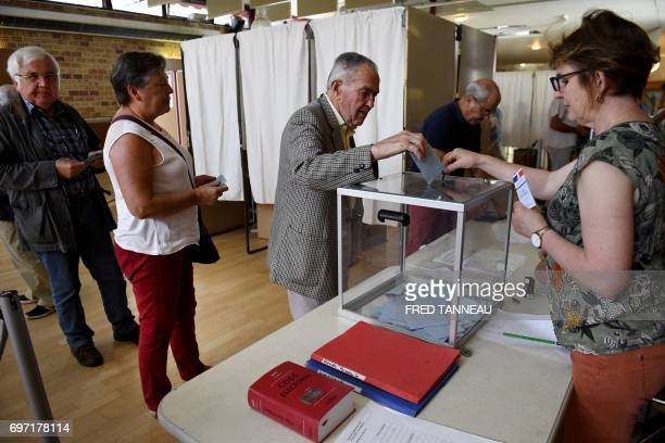 A man casts his vote at a polling station in CarhaixPlouguer western France during the second round of the French parliamentary elections on June 18...