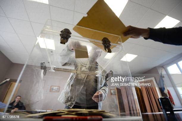 TOPSHOT A man casts his vote at a polling station in the small rural town of Le Pin western France on April 23 2017 during the first round of the...