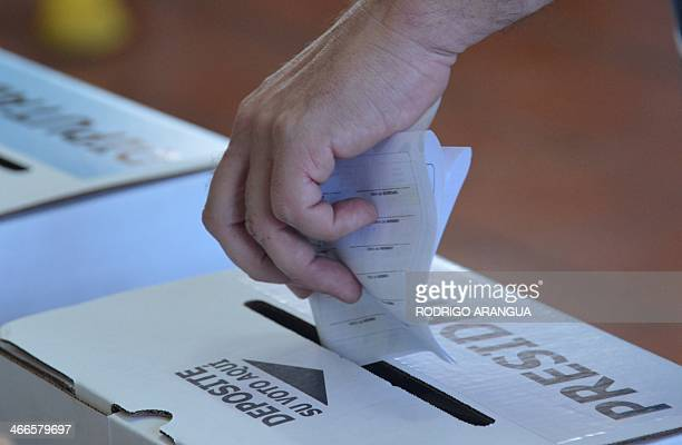A man casts his vote during the presidencial election on February 2 2014 in san Jose Costa Ricans pick a new president Sunday from a field of four...