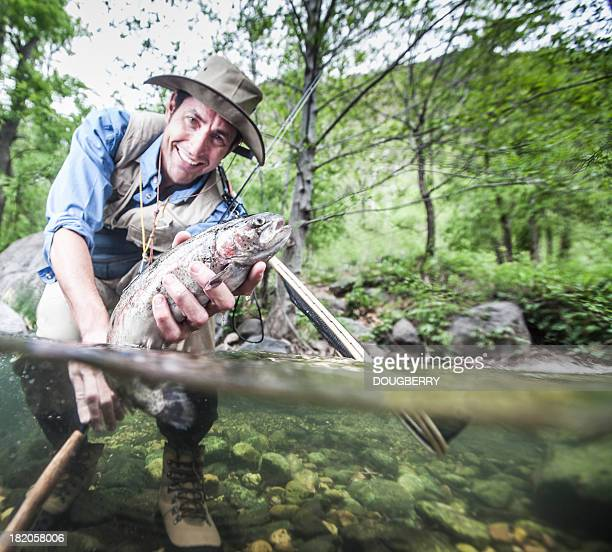 Man catching a Rainbow Trout fish