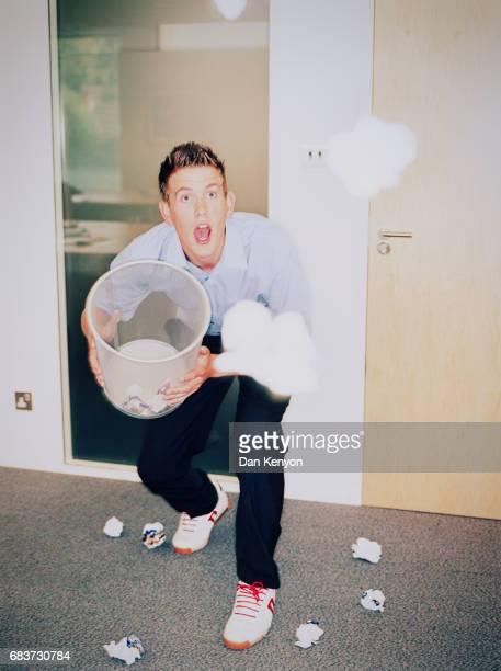 Man catching paper balls in waste paper basket.