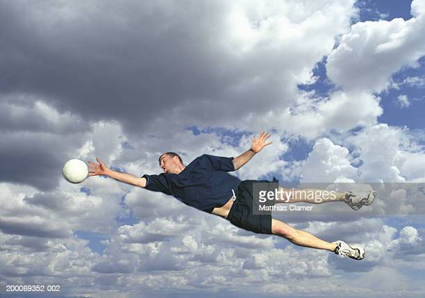 Man catching soccer ball in mid air