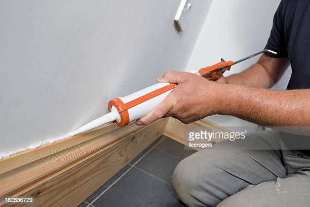 Man caulking between the wall and floorboards of a house