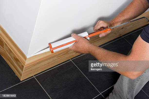 Man caulking wooden skirting in a new property