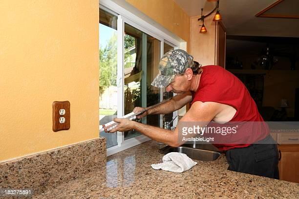 Man Caulks New Energy Efficient Windows in Kitchen