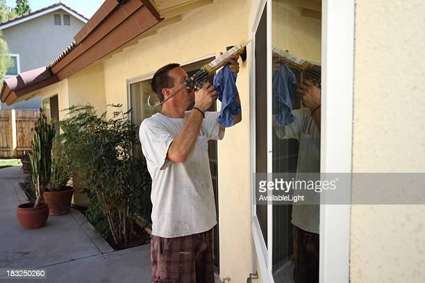Man Caulks New Energy Efficient Windows