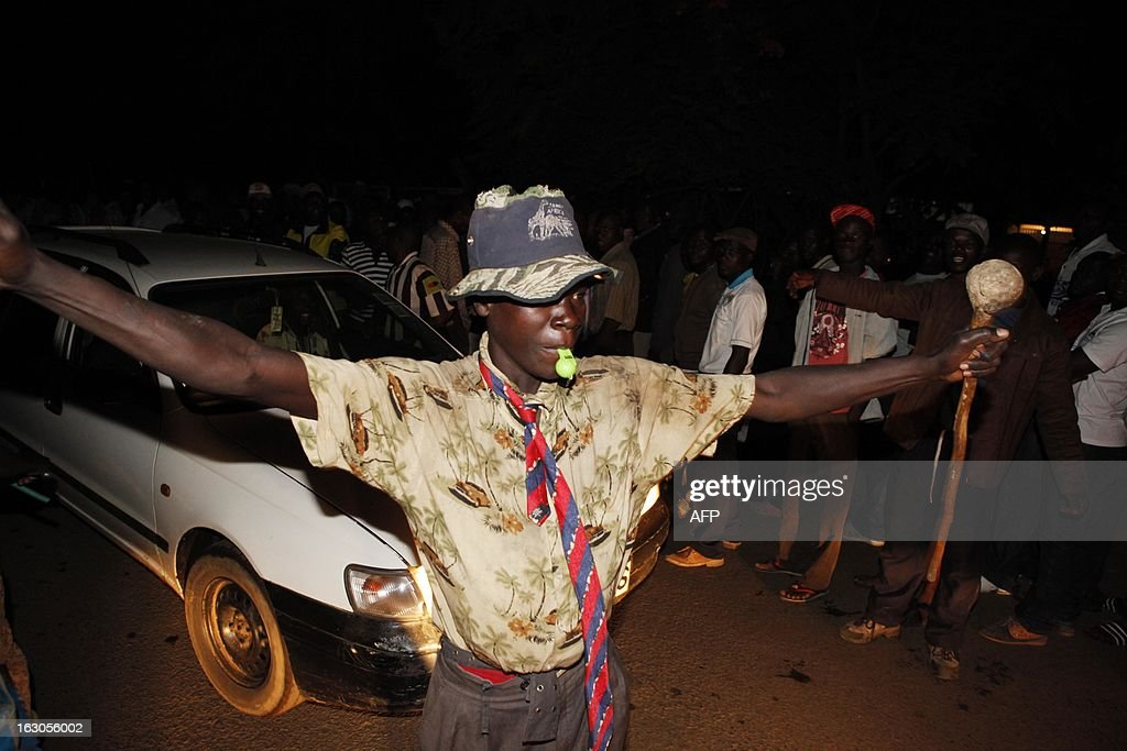 A man celebrates on the street in front of the Kisumu Social Centre, one of the largest polling stations in Kisumu town in western Kenya March 4, 2013. Kenyans go to the polls March 4, 2013 for the first time since bloody post-poll violence five years ago for which a top presidential candidate faces trial for crimes against humanity. Neck-and-neck rivals for the presidency, Prime Minister Raila Odinga and his deputy Uhuru Kenyatta, have publicly vowed there will be no repeat of the bloodshed that followed the disputed 2007 polls in which over 1,100 people died and some 600,000 were displaced. AFP PHOTO / Till MUELLENMEISTER