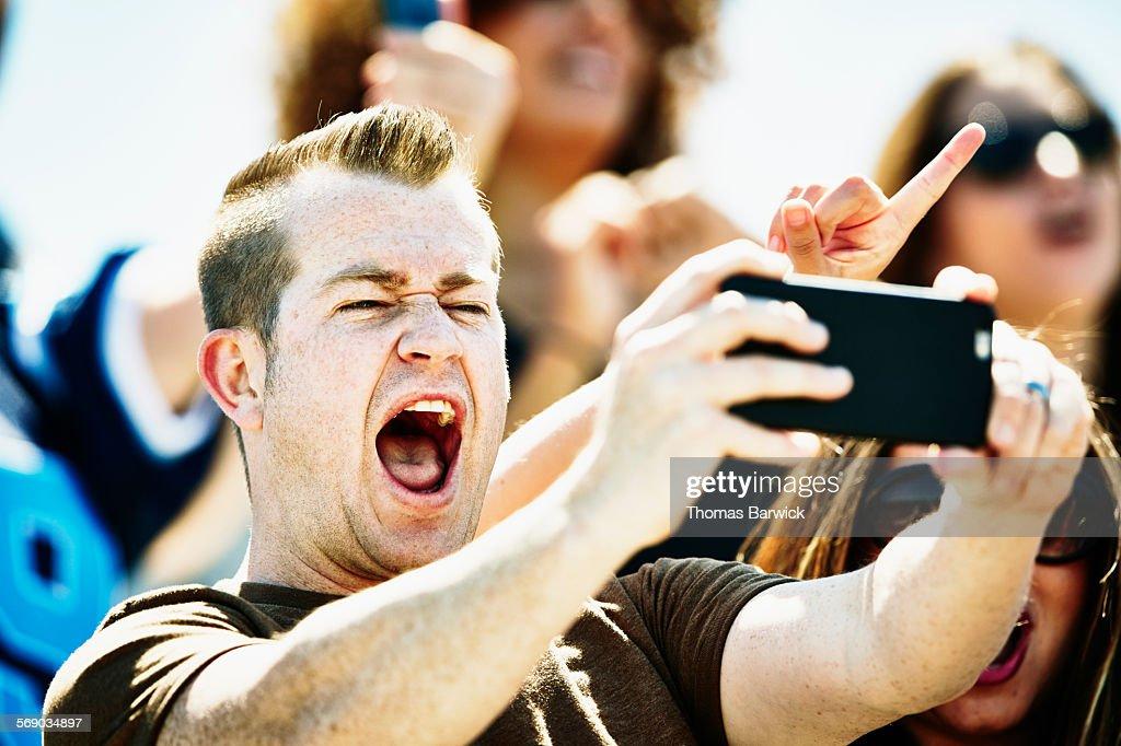 Man celebrating at football game taking selfie