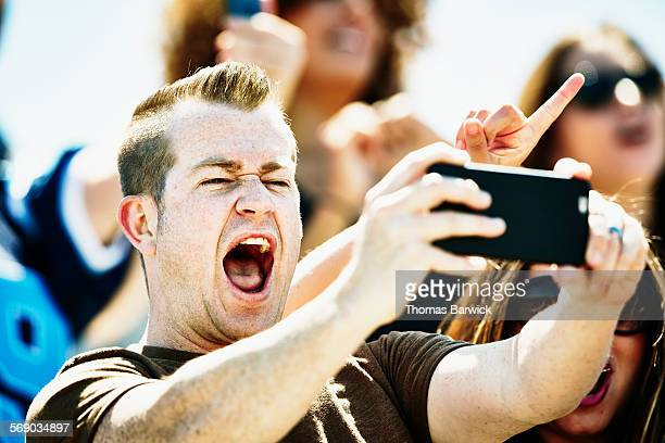 Man celebrating at football game taking selfie