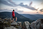 Man celebrating sunset looking at view in mountains. Trail runner, hiker or climber reached top of a mountain, enjoy inspirational landscape on rocky trail Karkonosze, Poland