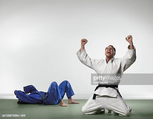 Man celebrating winning judo match while opponent covers face