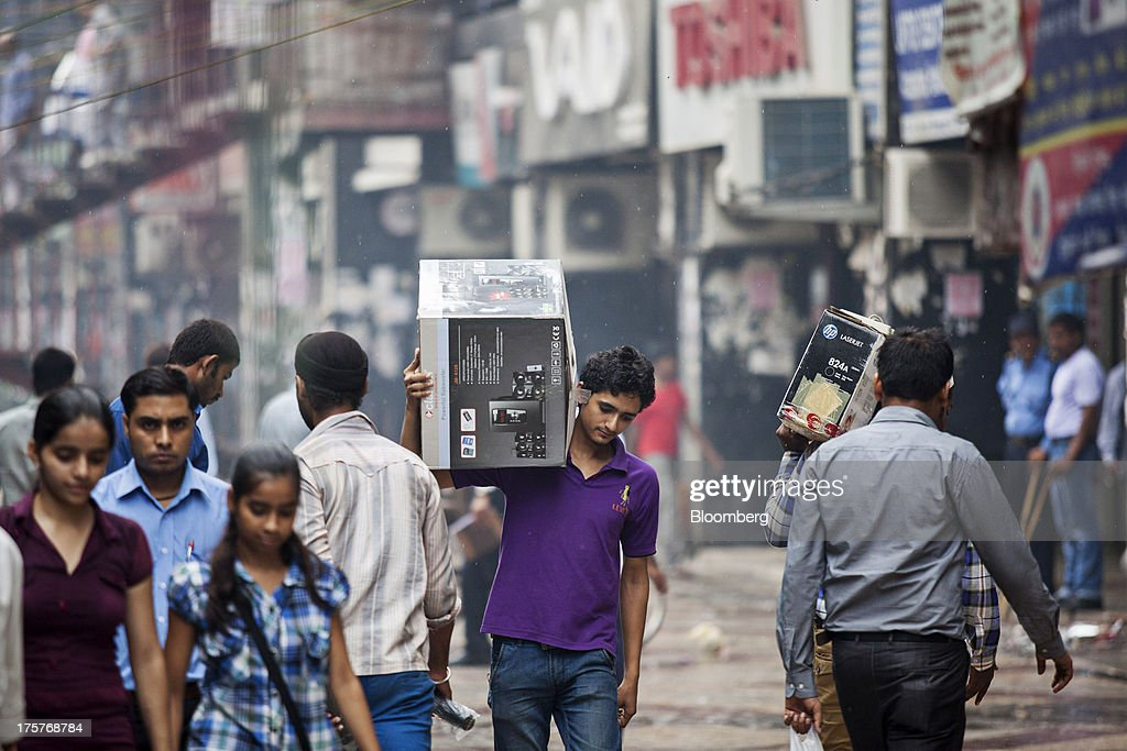 A man, center, carries a boxed Clarion Co, Ltd. subwoofer in Nehru Place IT Market, a hub for the sale of electronic goods and computer accessories, in downtown New Delhi, India, on Wednesday, Aug. 7, 2013. India's consumer price index (CPI) figures for July are scheduled to be released on August 12. Photographer: Graham Crouch/Bloomberg via Getty Images