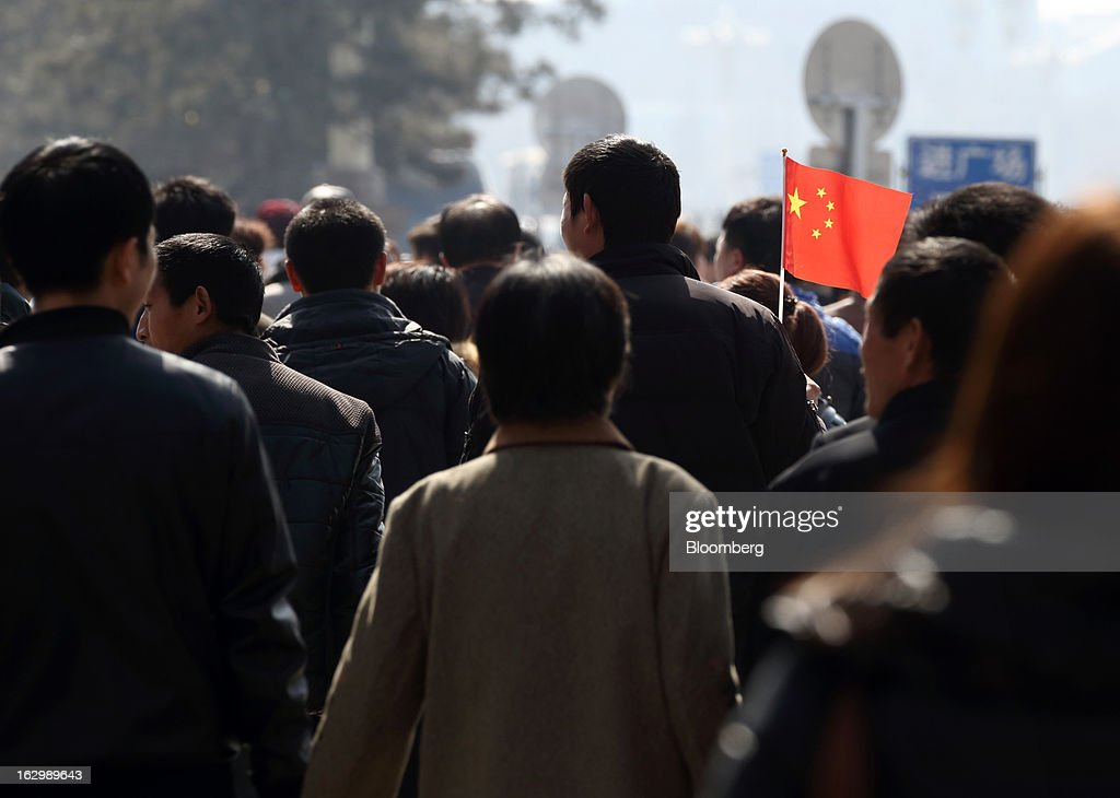 A man, center, holds a Chinese flag in Beijing, China, on Sunday, March 3, 2013. Premier Wen Jiabao will this week formally announce this year's economic targets when he delivers his final work report to the National People's Congress, which begins on March 5. Photographer: Tomohiro Ohsumi/Bloomberg via Getty Images