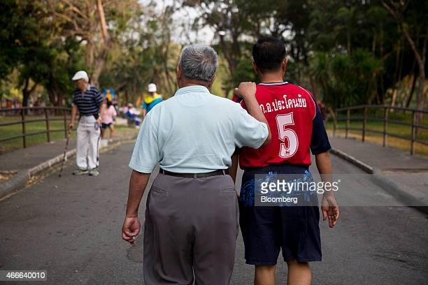 A man center left holds the shoulder of another as they walk through Lumphini Park in Bangkok Thailand on Sunday March 15 2015 Almost a third of...