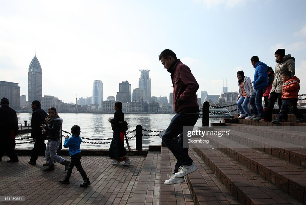 A man, center right, jumps as he walks down steps on the waterfront in the Pudong area of Shanghai, China, on Saturday, Feb. 9, 2013. China's services industries grew at the fastest pace since August as gains in retailing and construction aid government efforts to drive a recovery in the world's second-biggest economy. Photographer: Tomohiro Ohsumi/Bloomberg via Getty Images