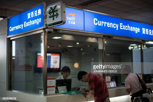A man changes foreign currency into Chinese yuan at a currency exchange office in Hongqiao airport in Shanghai on August 14 2015 China's central bank...