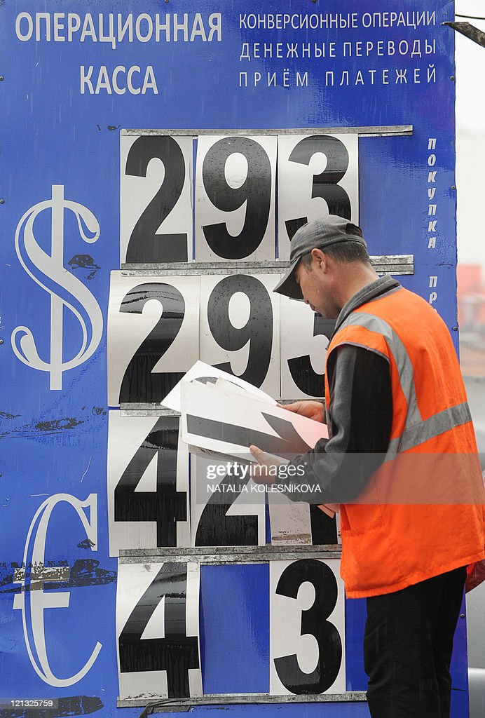 A man changes numbers on a display of a currency exchange bureau in Moscow on August 10 2011 as Russia's two main markets opened with gains of about...