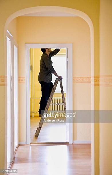 Man changing a light-bulb on a ladder