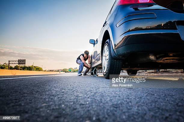 Homme changeant les compressé pneumatiques à l'autoroute
