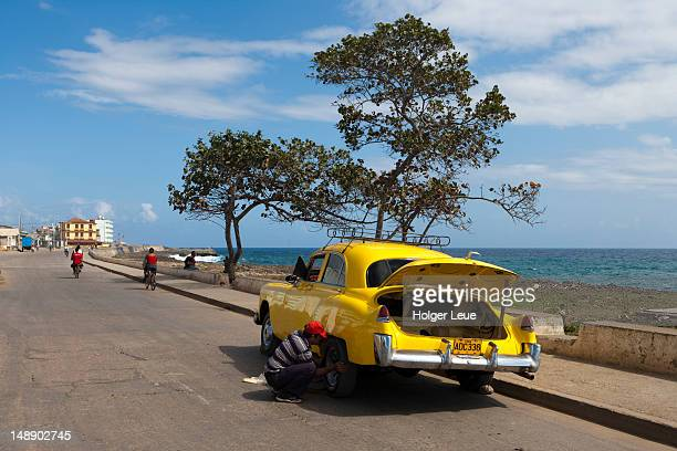 Man changing tyre on yellow car.
