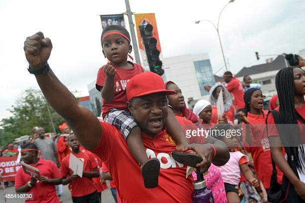 A man chant carrying his child on his shoulder during a rally to mark 500 days since the abductions of Chibok schoolgirls by Boko Haram militants as...