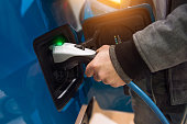 Man charging electro car at charging station. Man holding in hand power cable supply plugged in charging port.