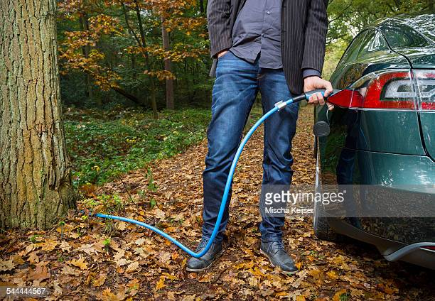 Man charging electric car in forest
