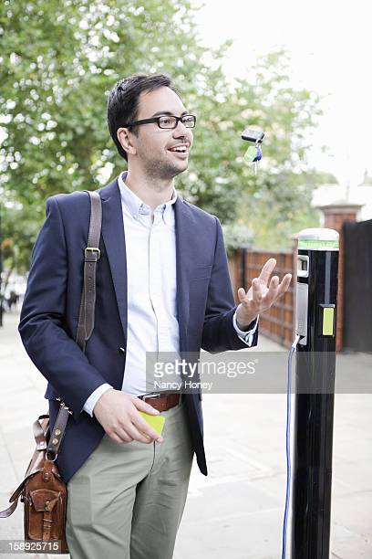 Man charging electric car on street
