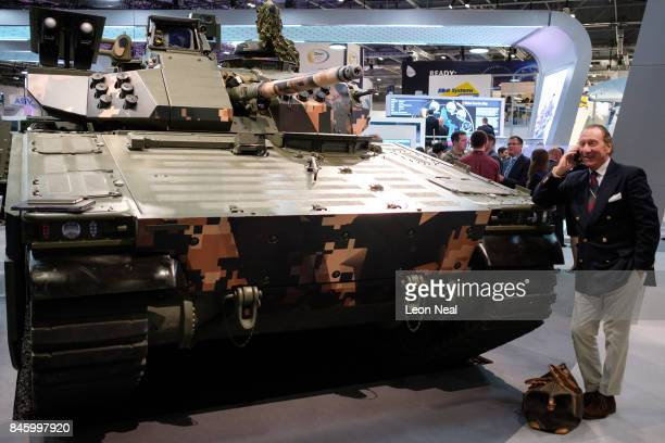 A man chats on his phone as he leans on a CV90 Battle Station in the 'BAE Systems' display area at the DSEI event at the ExCel centre on September 12...