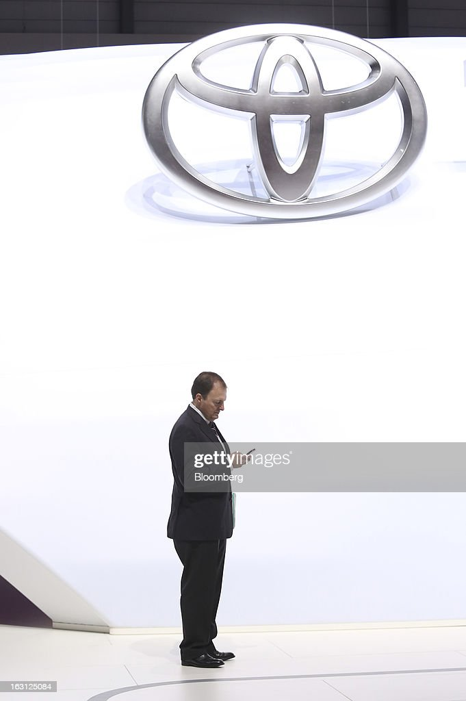 A man check his mobile phone below theToyota Motor Corp sign on the first day of the 83rd Geneva International Motor Show in Geneva, Switzerland, on Tuesday, March 5, 2013. This year's show opens to the public on Mar. 7, and is set to feature more than 100 product premiers from the world's automobile manufacturers. Photographer: Chris Ratcliffe/Bloomberg via Getty Images