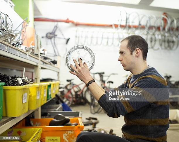 Man checking a bicycle part in workshop.