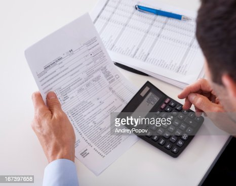 Man checking an invoice on a calculator : Stock Photo