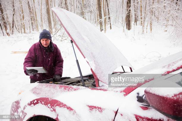 Man checking car engine after winter accident using tablet