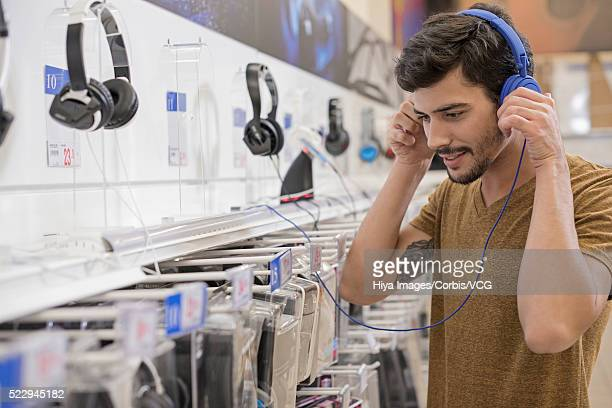 Man checking headphones in electronics store