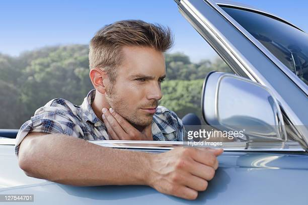 Man checking himself in car side mirror