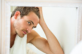 Reflection of young man checking his hair in front of bathroom mirror