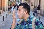 Man checking his own breath.