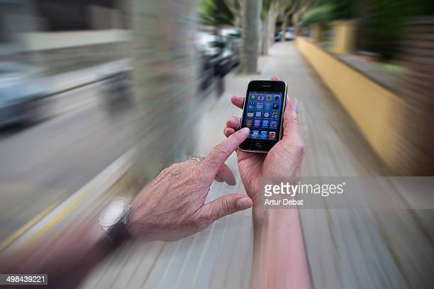 Man checking his smartphone in first person view while he is walking on the street Internet addiction