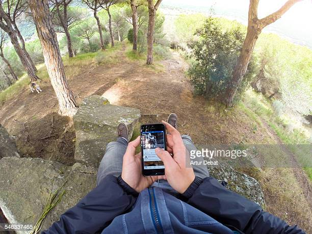 Man checking Internet with smartphone sitting on rock on the woodland nature from personal point of view