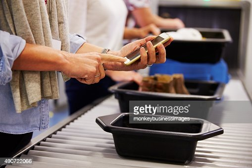 Man Checking Mobile Is Charged At Airport Security Check : Stock Photo